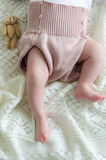 Tiny little babys feet in woolen shorts with a toy Royalty Free Stock Photo