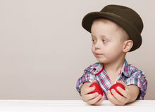 Tiny little boy in a hat looks left in hands holding red Easter Stock Image