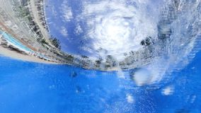 Man jumps into swimming pool water at modern hotel. Tiny little planet 360 degrees young man in glasses jumps into swimming pool water at modern hotel stock video footage