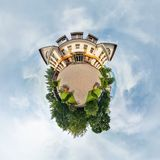 Tiny little planet with trees near beautiful building, white clouds and soft blue sky of amusement park. 360 degrees viewing angel stock photo