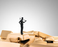 Tiny man with a pickaxe on top of a pile of gold Royalty Free Stock Photos