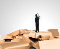 Tiny man with a pickaxe on top of a pile of gold Stock Photo
