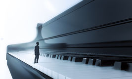 Tiny man standing on a piano Stock Photos