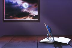 Tiny man writing heart on book among light of full moon. And romantic mid night moon light pass window drop to this man over book Royalty Free Stock Image