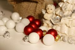 A porcelain figurine surrounded by tiny Christmas baubles in red and white. royalty free stock photos