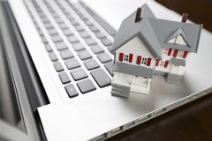 Tiny Miniature House on a Laptop Computer Royalty Free Stock Image