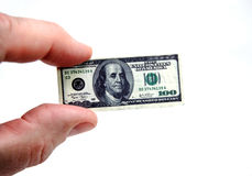 Tiny Money. Index finger and thumb holding a minature version of a hundred dollar bill Royalty Free Stock Photos