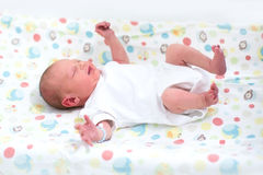 Tiny newborn baby on a changing table Stock Photo