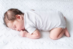 Tiny newborn baby sleeping on knitted blanket. Tiny newborn baby sleeping on a white knitted blanket Royalty Free Stock Image
