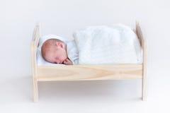 Tiny newborn baby sleeping in a toy crib stock photo