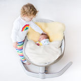 Tiny newborn baby in swing with his toddler sister Royalty Free Stock Image