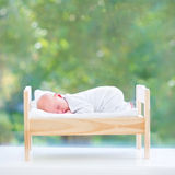 Tiny newborn baby in toy bed next to big window Stock Photos