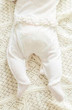 Tiny newborn babys feet in spotted romper suit on woolen blanket Royalty Free Stock Photography