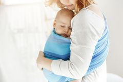 Tiny newborn child close eyes and having good sleep in baby sling feeling protection from his beautiful young mother. Tiny newborn child close eyes and having stock photos