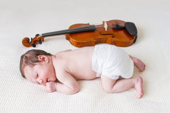 Tiny newborn girl lying next to a violin Stock Photos