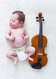 Tiny newborn girl lying next to a violin Royalty Free Stock Image
