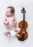 Tiny newborn girl lying next to a violin. Tiny newborn baby lying next to a violin royalty free stock image