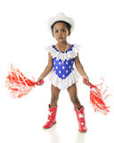 Tiny Patriot Celebrating. An adorable African American patriot shaking pom-poms whiel dressed in a star studded, red, white and blue western outfit.  On a white Royalty Free Stock Photos
