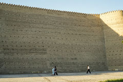 Tiny people by the Ark Walls in Bukhara Uzbekistan Stock Photo