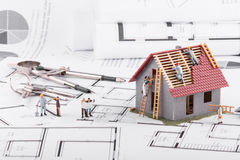 Tiny people build houses for architectural plans. The concept of. Teamwork Royalty Free Stock Image