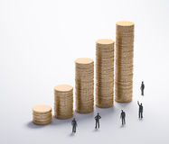 Tiny people and gold coins Stock Images