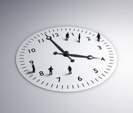 Tiny people standing around a clock. Time and schedule in the workplace concept Royalty Free Stock Images
