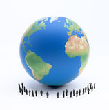 Tiny people standing around Earth Royalty Free Stock Photos