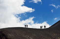 Tiny people on the volcanic slope Stock Photo