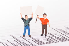 Tiny person demonstrating on a graph Stock Image