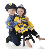 Tiny Public Servants. Little brothers posing together, the little one dressed as a fireman, the older his big brother dressed as a policeman.  On a white Stock Photography