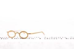 Tiny reading glasses on text Stock Image