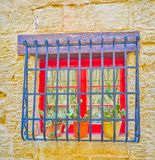 The tiny red window, Naxxar, Malta. The tiny red window behind the bars and cactuses in pots of residential house in Naxxar town, Malta stock image