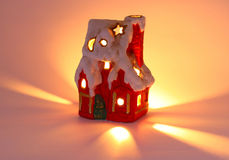 Tiny red xmas house and candle. Tiny red xmas house with chimney, snow and candlelight stock photo