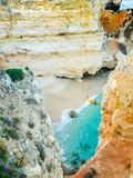 Tiny remote beach in Lagos, Algarve, Portugal. A hidden secret beach between limestone walls. People with a yellow kayak visiting. Tiny remote beach in Lagos Royalty Free Stock Photography