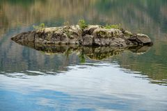 Tiny rock in the middle of a lake Royalty Free Stock Image