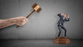 A tiny scared businessman stands on a giant sound block under a large hand holding a judge gavel. royalty free stock photo