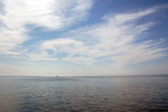 Tiny ship in the horizon under cloudy sky Stock Photography