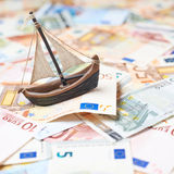 Tiny ship over the bank note bills Royalty Free Stock Image