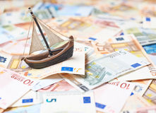Tiny ship over the bank note bills Stock Image