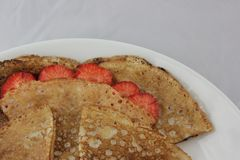 White plate and tiny pancakes with strawberries stock image