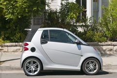 Tiny Smart Car. A tiny, silver, subcompact Smart Car, parked on a residential street Stock Image