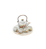 Tiny souvenir teapot with bowls. Tiny souvenir teapot on a plate with four tiny bowls Royalty Free Stock Images