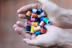 Tiny spools in hands Royalty Free Stock Photography