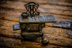 Tiny Stove. Tiny child's antique stove pictured on textured wood Royalty Free Stock Photo