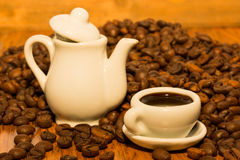 A tiny teapot with a cup of morning coffee. White teapot and a cup of morning coffee among fragrant coffee beans close-up at a wooden background Royalty Free Stock Photography