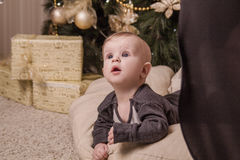 Tiny toddler looks up in surprise near the Christmas tree royalty free stock image
