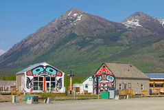 The tiny town of carcross with snow-capped mountains in the background. Buildings with aboriginal art at a village in the yukon Royalty Free Stock Image