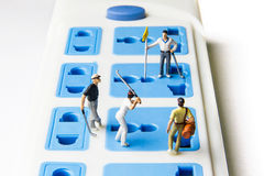 Tiny toy golfers on the extension power strip. Stock Photo
