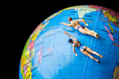 Tiny toy swimming on the globe world map. Stock Photography
