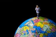 Tiny toy travel on the globe world map. Royalty Free Stock Photography